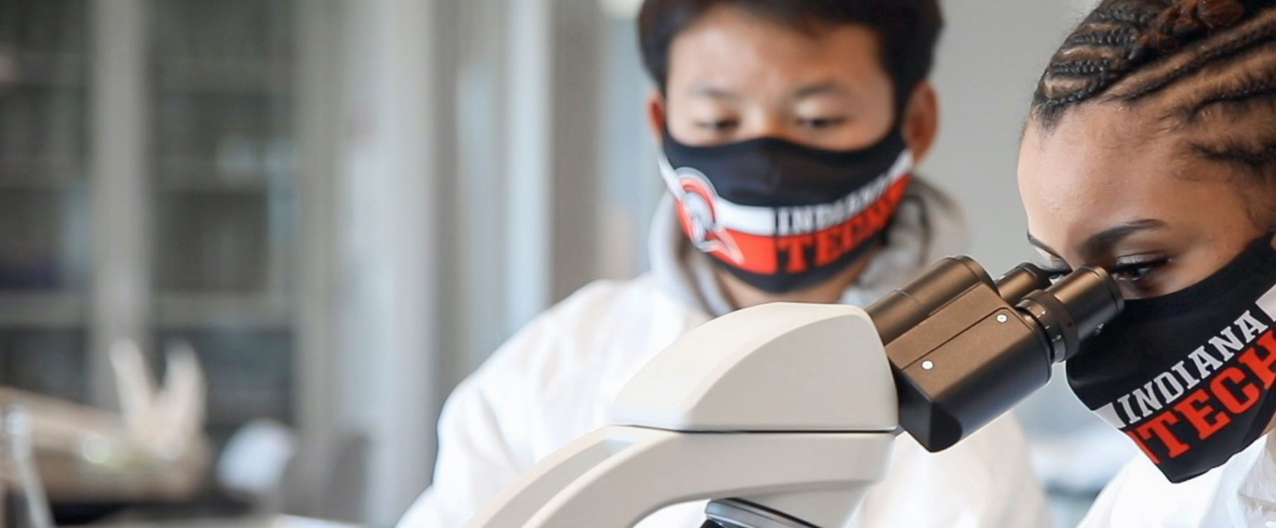 Students in masks using a microscope